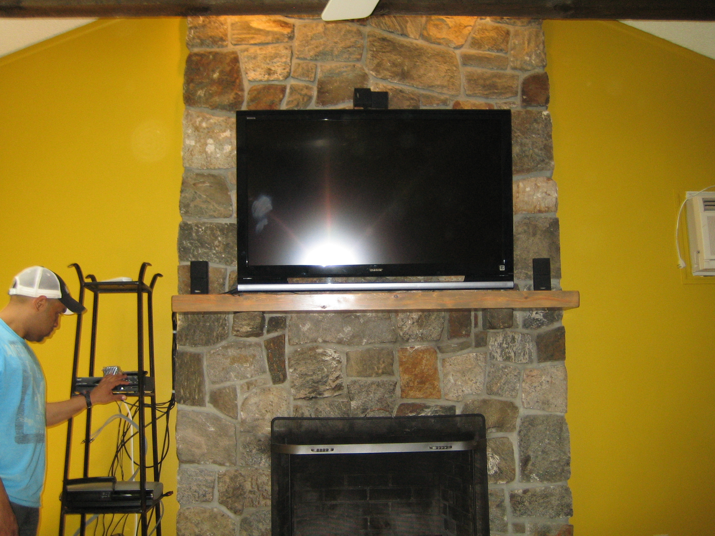 canaan, ct – tv install on natural stone above fireplace with