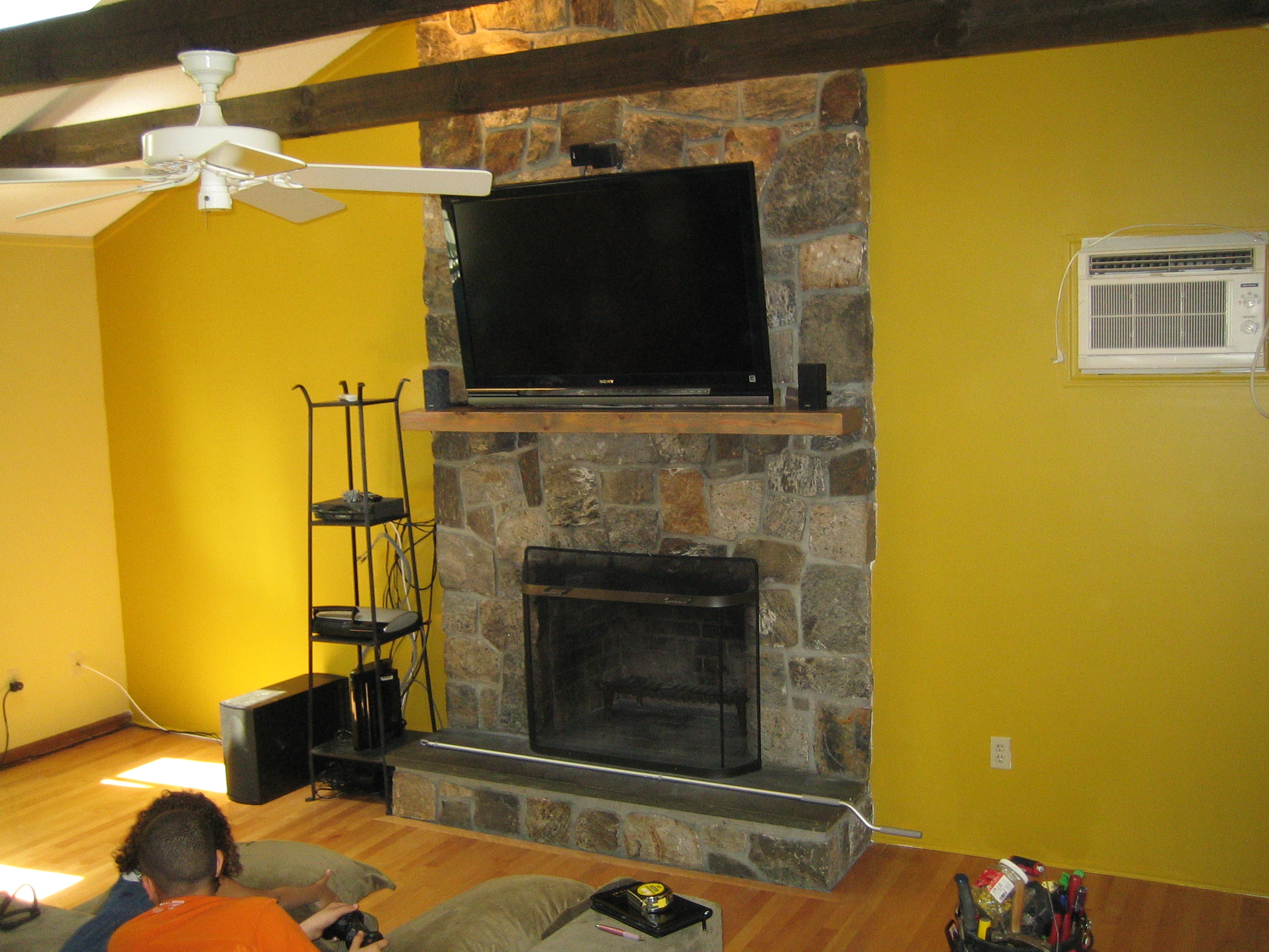 CT – TV Install on natural stone above fireplace with surround sound | Home Theater Installation